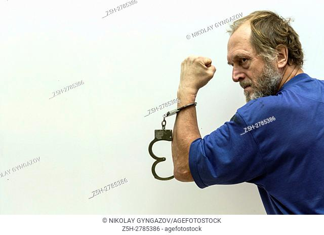 Elderly man handcuffed
