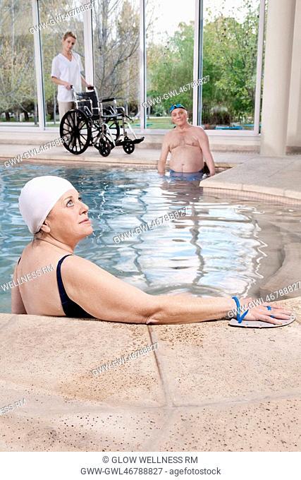 Woman wearing swim paddles in a swimming pool
