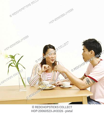 Young woman and a mid adult man looking at each other