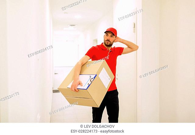 delivery, mail, people and shipment concept - confused man in red uniform with parcel box and clipboard in corridor