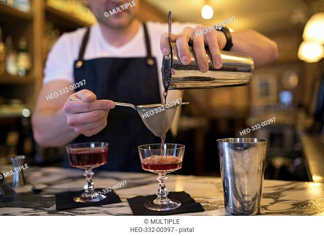 Male mixologist pouring cocktails through strainer into couple glasses in bar