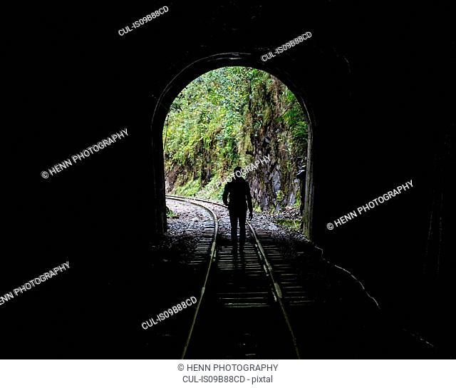 Hiker on train tracks that lead up to Aguas Calientes - the starting point for excursions to Machu Picchu, Peru