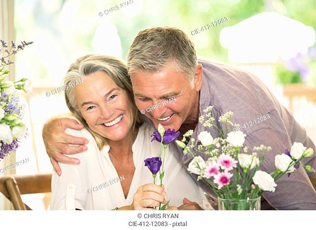 Senior couple smelling flowers