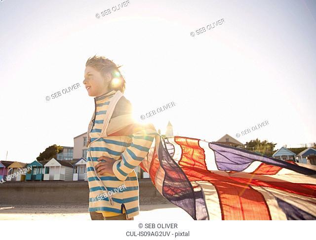 Boy at coast with union jack flag, Southwold, Suffolk, UK