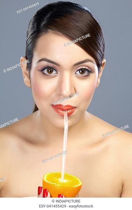 Portrait of a woman drinking juice from an orange