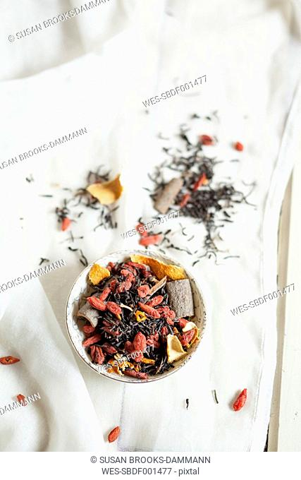Bowl of black spice tea with dried Goji berries, Lycium barbarum, on white cloth