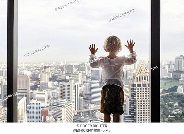Thailand, Bangkok, little girl looking through window at cityscape