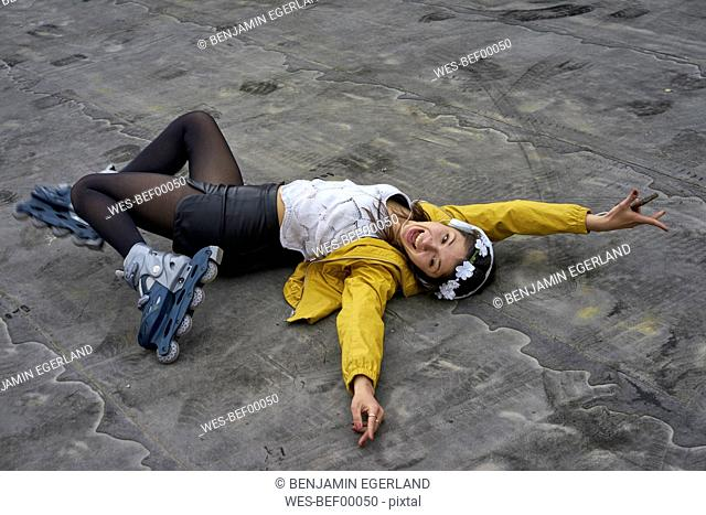 Screaming young woman with inline skates lying on ground listening music with headphones