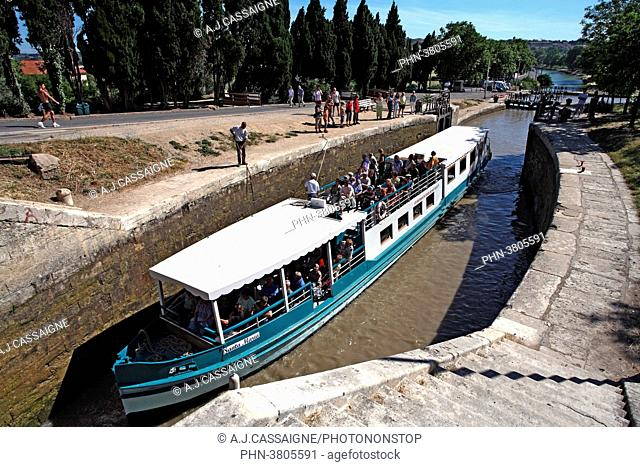 France, Southern France, Canal du Midi. Fonseranes lock near Beziers with a touristic boat going through the round lock. White and blue boat view from above to...