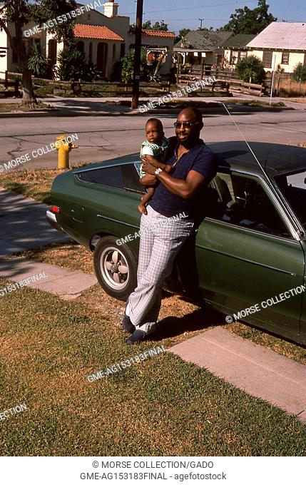 Portrait of an African American man posing with an African American infant boy in his arms, as he leans against a car parked in the driveway of a residential...