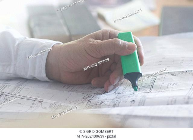 Cropped image of a businessman with highlighter working on blueprint in the office, Freiburg im Breisgau, Baden-Württemberg, Germany