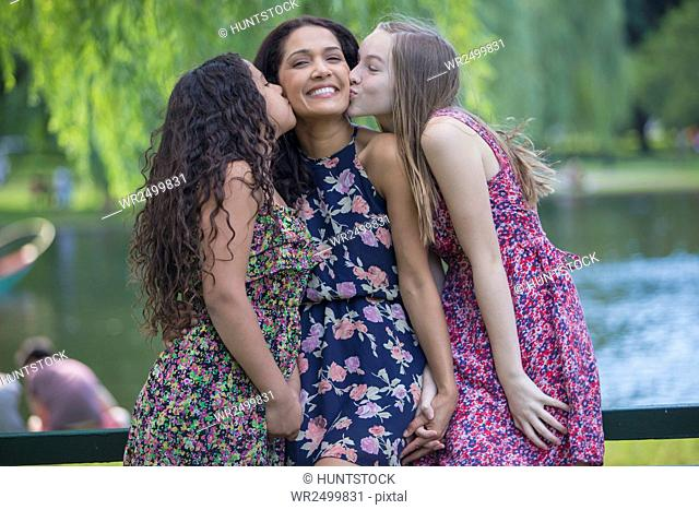 Happy Hispanic mother being kissed by two teen daughters in park