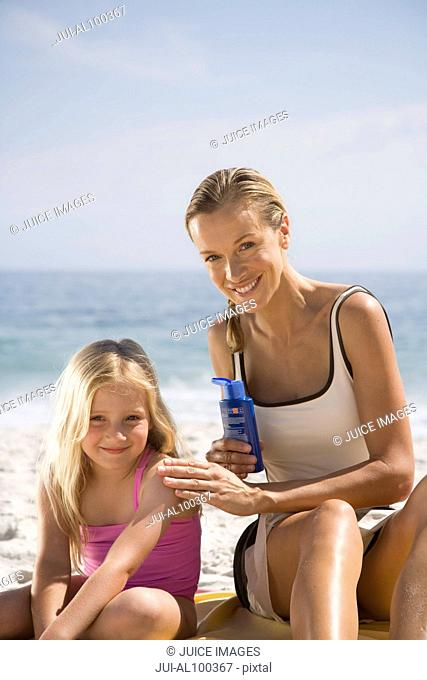 Mother putting sun screen on daughter at beach