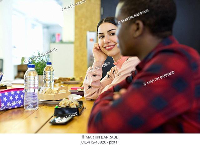 Smiling businesswoman listening to businessman, eating lunch in office