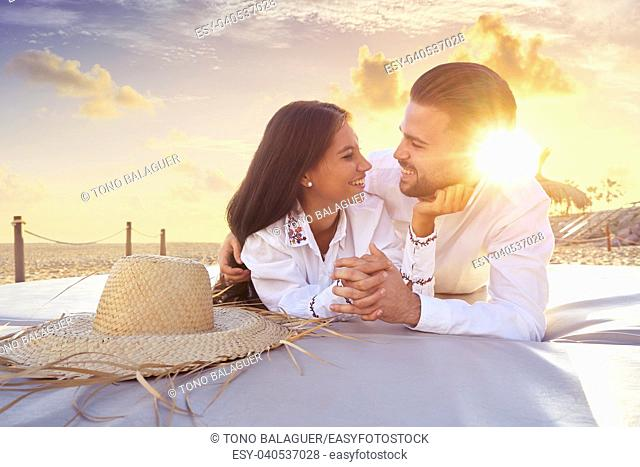 Couple young on beach lounge sunset vacation