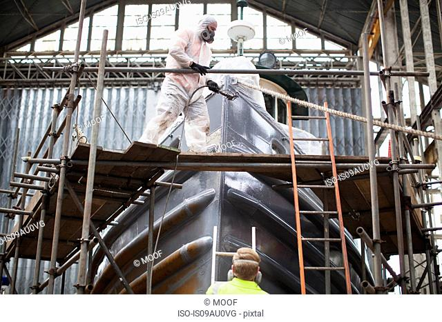 Workers spray-painting boat in shipyard