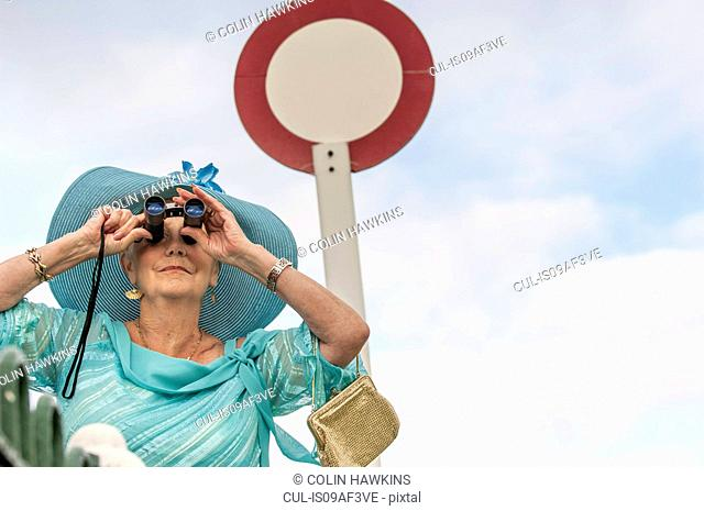 Senior woman at races looking through binoculars