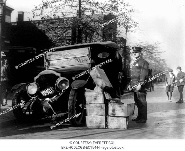 Prohibition, a policeman standing alongside a wrecked car and cases of moonshine, November 16, 1922