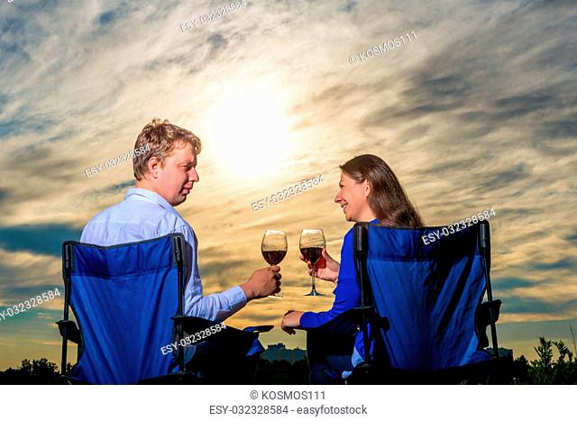 happy young married couple with a glass of wine at sunset