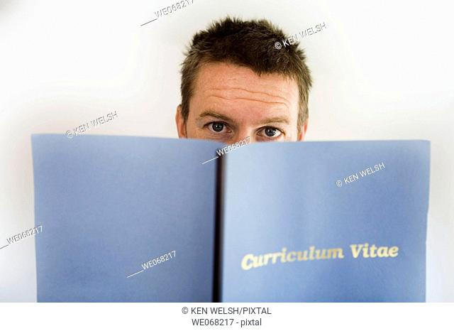 Man looking up from behind Curriculum Vitae folder