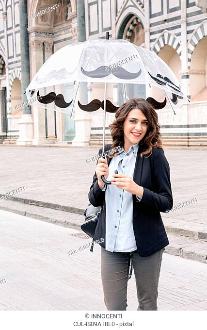 Young woman holding umbrella looking at camera smiling, Piazza Santa Maria Novella, Florence, Tuscany, Italy