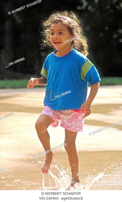 prk-scene, portrait, brown girl with long brown hair, 8 years, runs bare feeted through a puddle in summer  - GERMANY, 25/05/2003