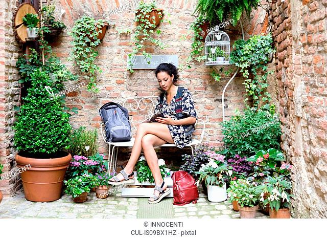 Woman enjoying peaceful corner with plants, Città della Pieve, Umbria, Italy