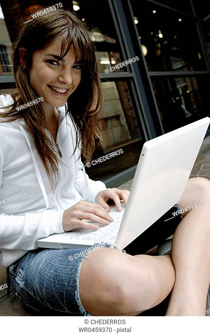 Portrait of a young woman smiling and working on a laptop