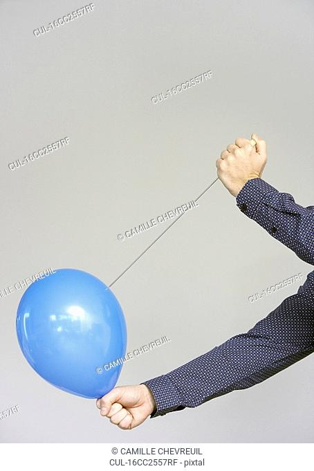 men's hands about to burst a balloon