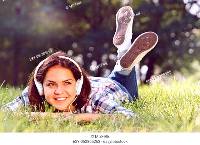 Close up portrait of Pretty young girl listening music lying at the grass. Cute teenage girl relaxing in park
