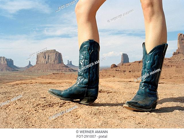 Woman standing in desert wearing cowboy boots