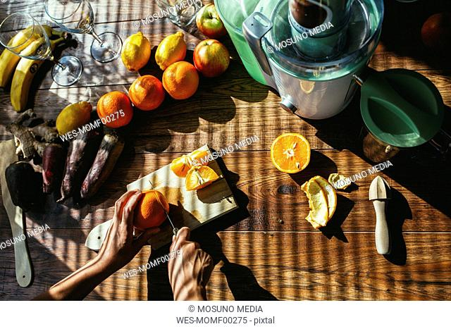 Woman's hands preparing fruits for squeezing juice