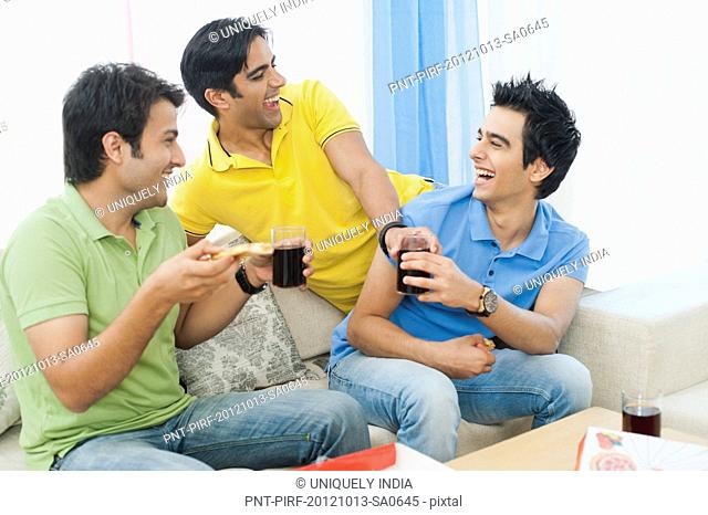 Friends enjoying pizza with soft drinks and smiling at home
