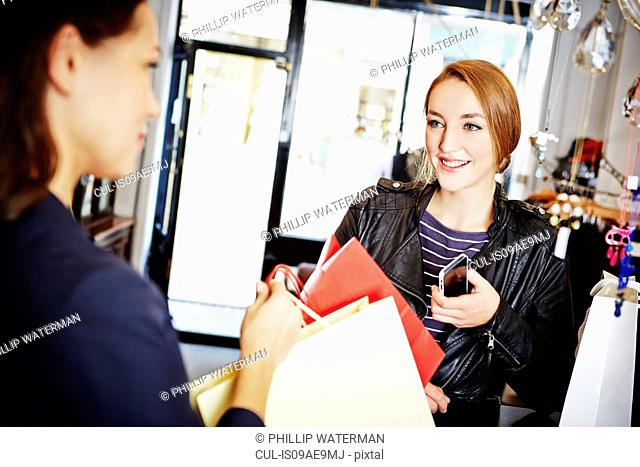 Young women in shop with shopping bags and smartphone