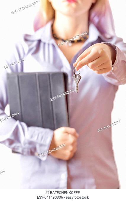 woman in a shirt with a tablet holds out the keys. Girl gives keys