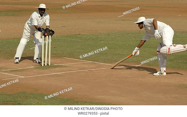 Batsman run out by wicket-keeper bat short of crease bells removed by red cricket ball hitting stumps on pitch in cricket match MR705-J,705L