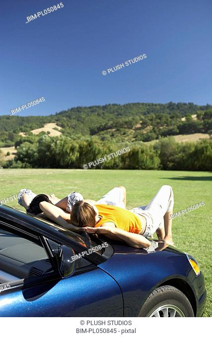 Couple relaxing on the hood of a car
