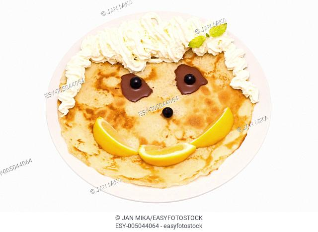 Happy face made up from crepe, lemons, blueberries, chocolate, mint and cream Image is isolated on white background, contains clipping path