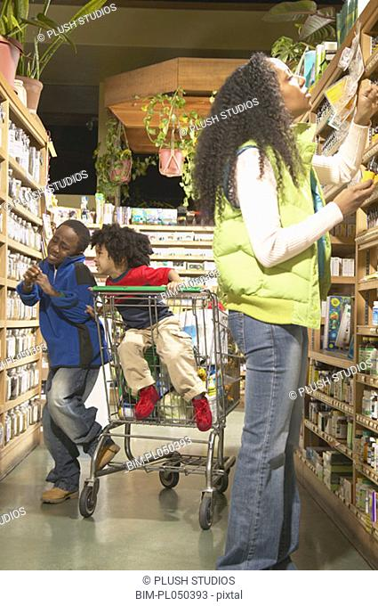 African American mother with young sons in health food store