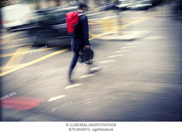 Unrecognizable man crossing the street among traffic. London, England