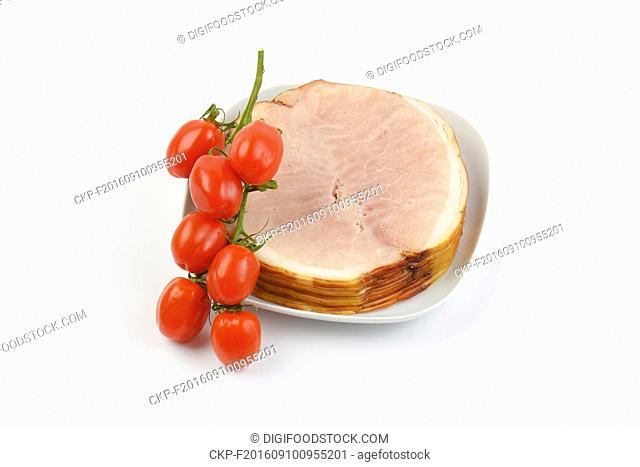 stack of ham slices and cherry tomatoes on white plate