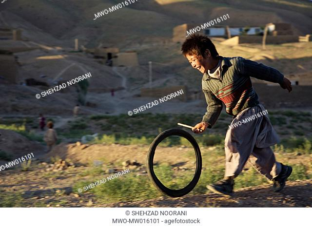 A laughing boy chases a bicycle inner tube with a stick, in the village of Ragshad, on the outskirts of Bamyan City in the central Bamyan Province He is a...