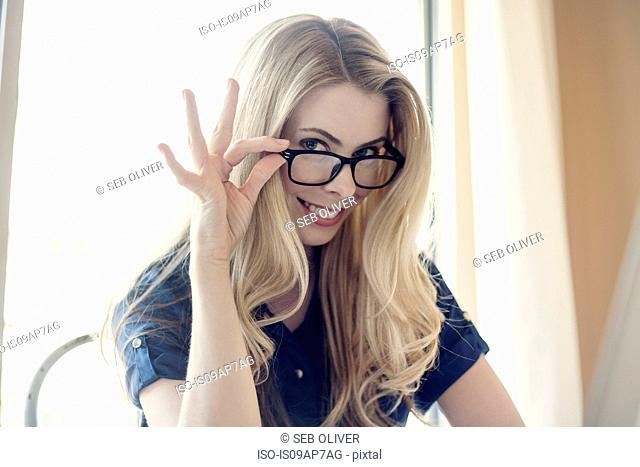 Mid adult businesswoman, looking over eyeglasses, smiling
