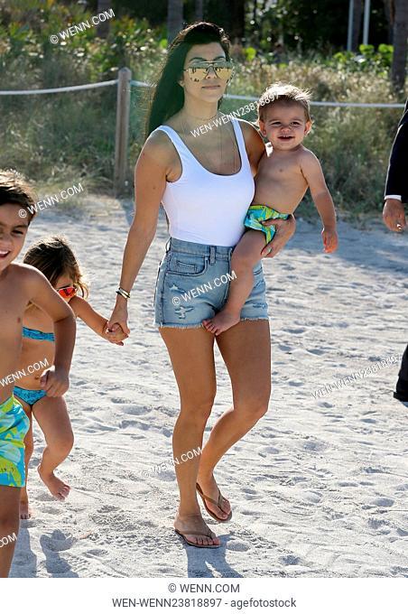 Kourtney Kardashian wears a white one piece swimsuit and denim hotpants as she takes her kids to the beach in Miami Featuring: Kourtney Kardashian