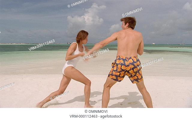 MS / Young couple fighting playfully on beach