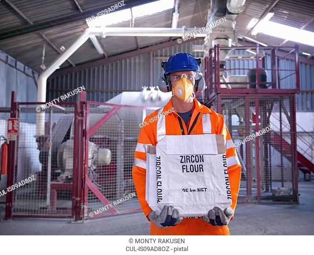 Worker in protective clothing holding zircon flour bag in mill