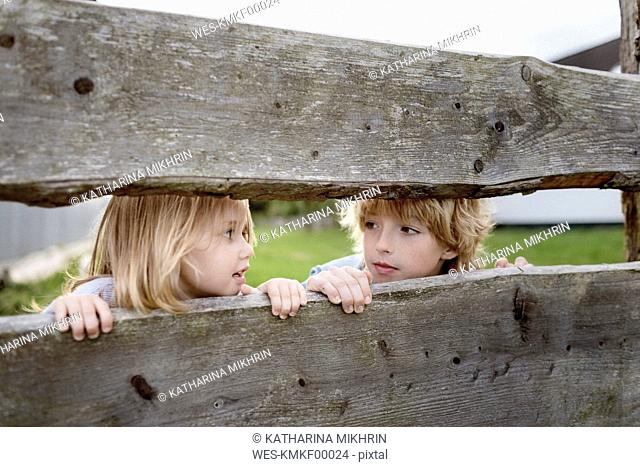 Brother and his little sister behind wooden fence