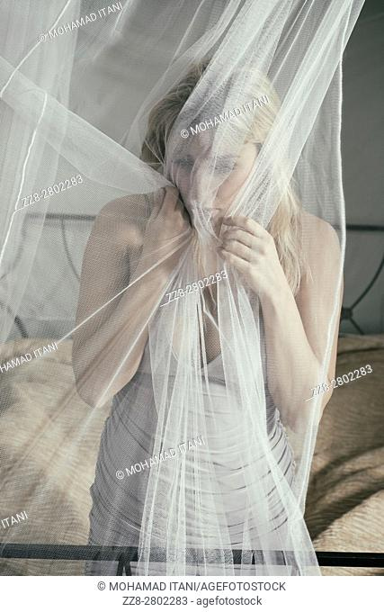 Scared woman grabbing the net on the bed