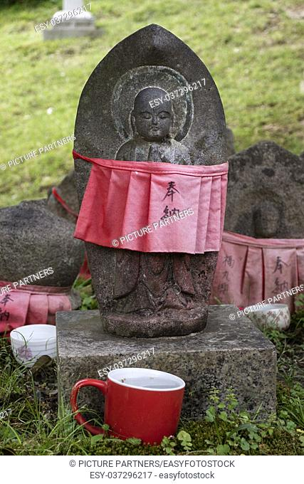 Traditional stone carved Jizo with red skirt honored and respected with a cup of water
