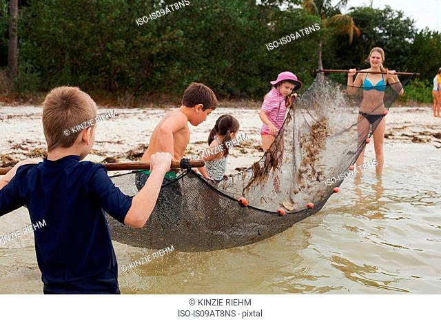 Teacher showing children how to use traditional fish net in an estuary, Sanibel Island, Pine Island Sound, Florida, USA